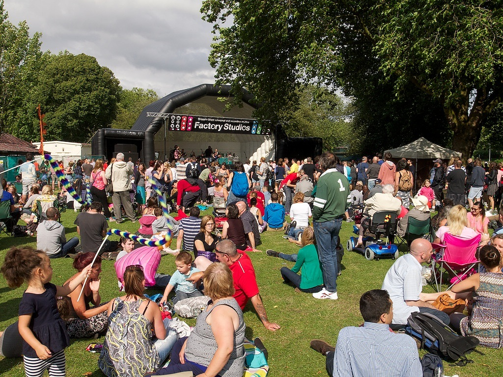 Revellers of many different ages and abilities sit or stand in the sun watching the main stage