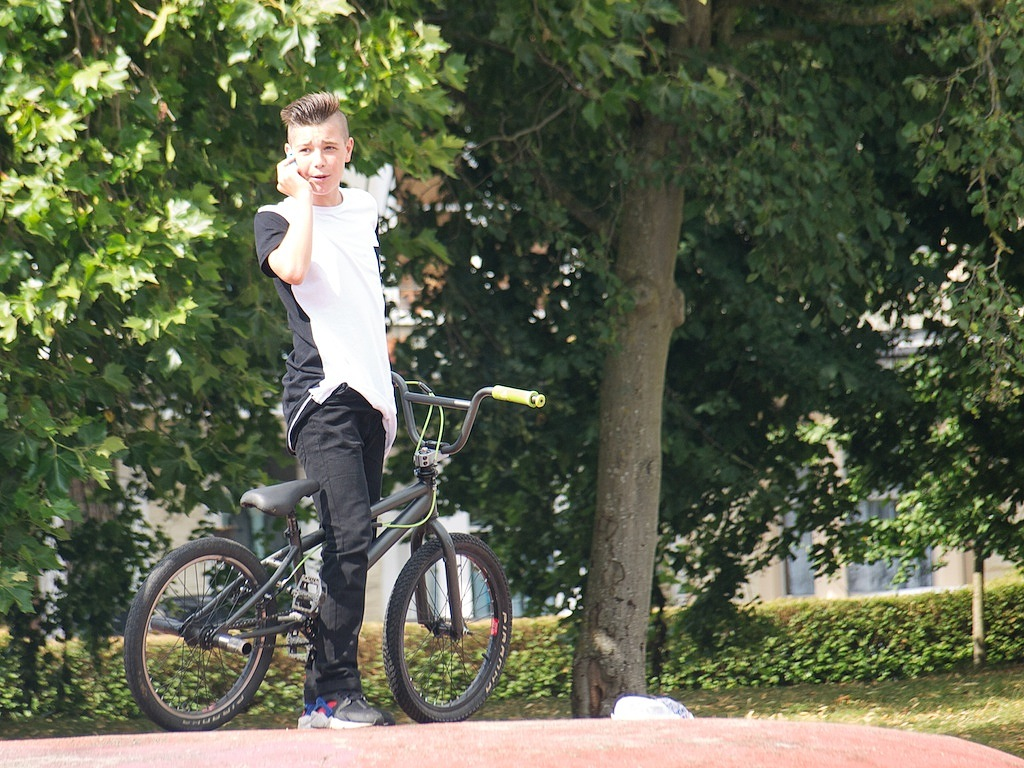 A young man stands with his BMX bike on the skate park. He is talking on the phone. There are trees behind