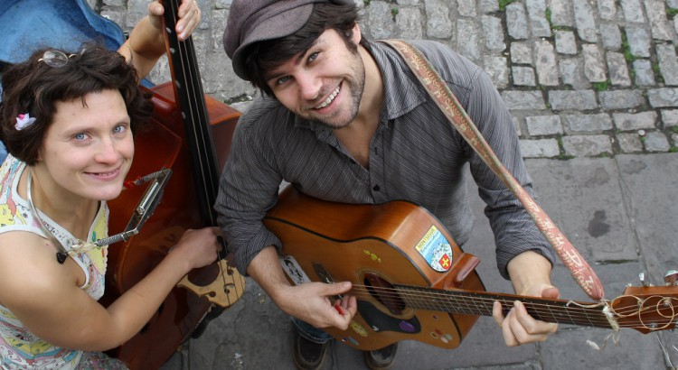 A man and a woman are shot from above, smiling broadly. She plays a double bass and harmonica, he plays an acoustic guitar.